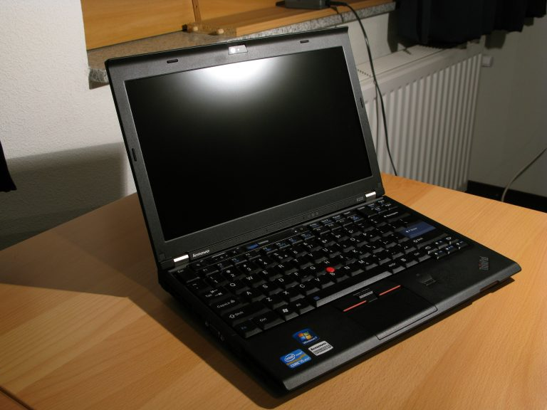 An open laptop computer sitting on top of a wooden table