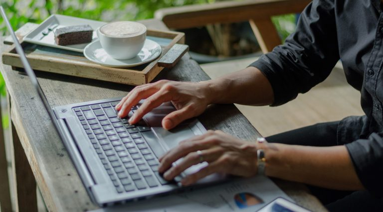 A person using a laptop computer sitting on top of a table