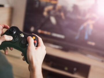 A person holding a video game remote and playing video game