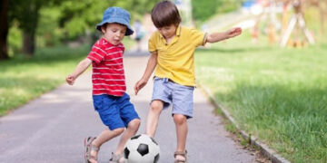 kids playing a football on road